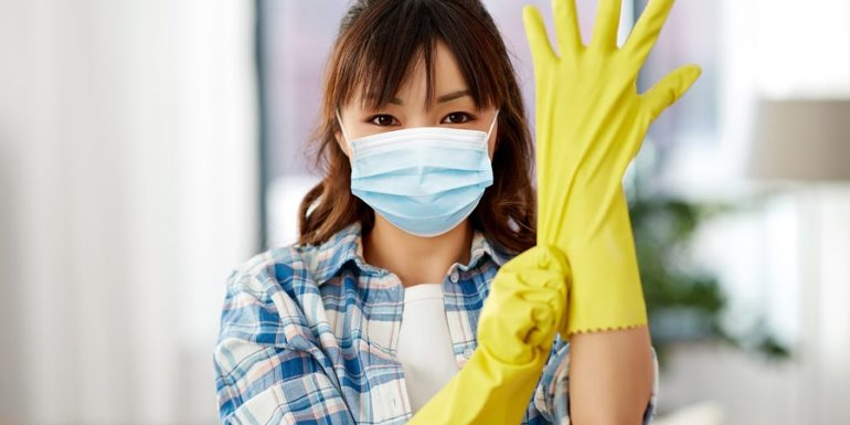 lady with mask and cleaning yellow gloves on to disinfect the house